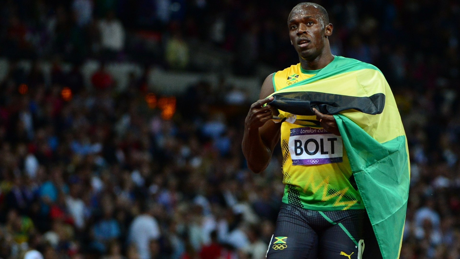 Usain Bolt carrega bandeira jamaicana após se tornar bicampeão olímpico dos 100 m rasos
