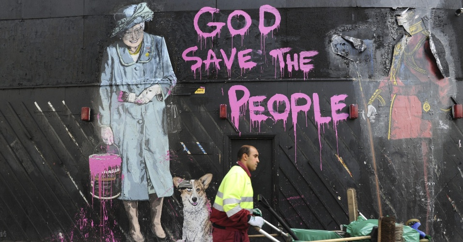 06.ago.2012 - Mural em rua de Londres traz desenho da Rainha Elizabeth 2&#170; ao lado da frase God Save the People (&#34;Deus salve o povo&#34;), inspirado na frase &#34;God Save the Queen&#34; (Deus salve a rainha). Entre 4 a 8 de agosto, os ingleses relembram um ano das manifesta&#231;&#245;es e dist&#250;rbios que tomaram o centro de Londres e cidades pr&#243;ximas, desencadeadas ap&#243;s a morte de um jovem pela pol&#237;cia brit&#226;nica, no barrio de Tottenham