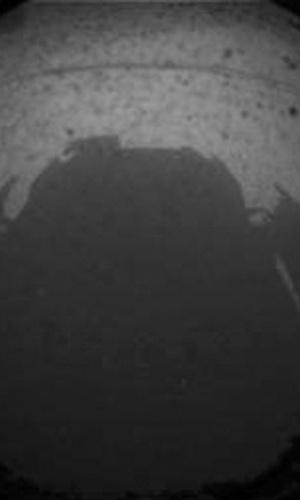 """6.ago.2012 - As primeiras imagens enviadas pela """"Curiosity"""" foram assim, em preto e branco. Na foto grande-angular, é possível ver a sombra do próprio jipe-robô, que tem como missão principal descobrir vestígios de vida no planeta vizinho"""