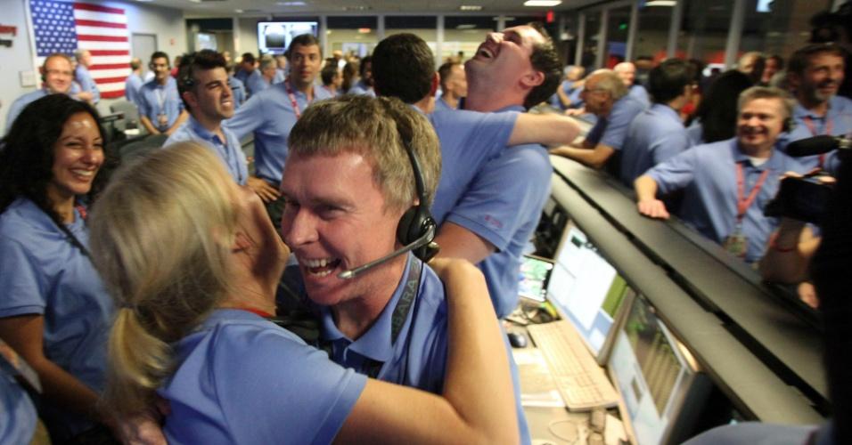 6.ago.2012 - O engenheiro de telecomunicações Peter Ilott abraça uma colega ao celebrar o pouso do robô Curiosity em uma cratera de Marte. A missão não tripulada estudará a possibilidade de ter havido vida no planeta vermelho
