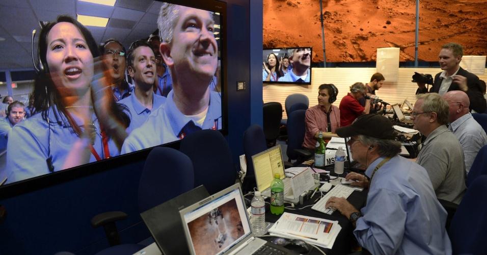 """6.ago.2012 - Trabalhadores do laboratório da Nasa (agência espacial americana) comemoram o pouso do robô Curiosity em uma cratera de Marte. A descida pela atmosfera do planeta foi chamada de """"sete minutos de terror"""" por conta das manobras de alto risco que reduz"""
