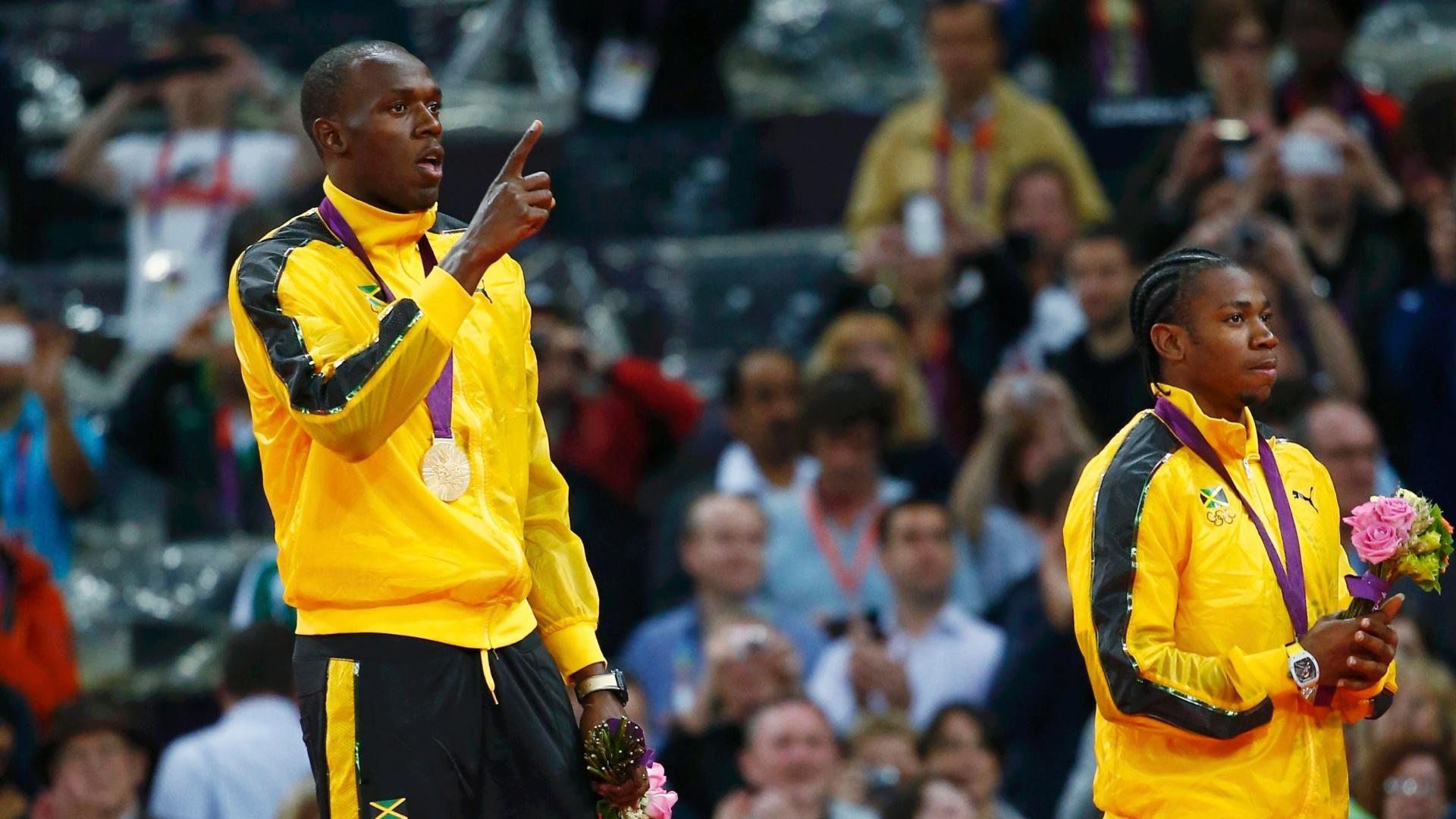 Ao lado de Yohan Blake, Usain Bolt faz sinal de número 1 em cerimônia de premiação dos 100 m rasos nos Jogos de Londres-2012