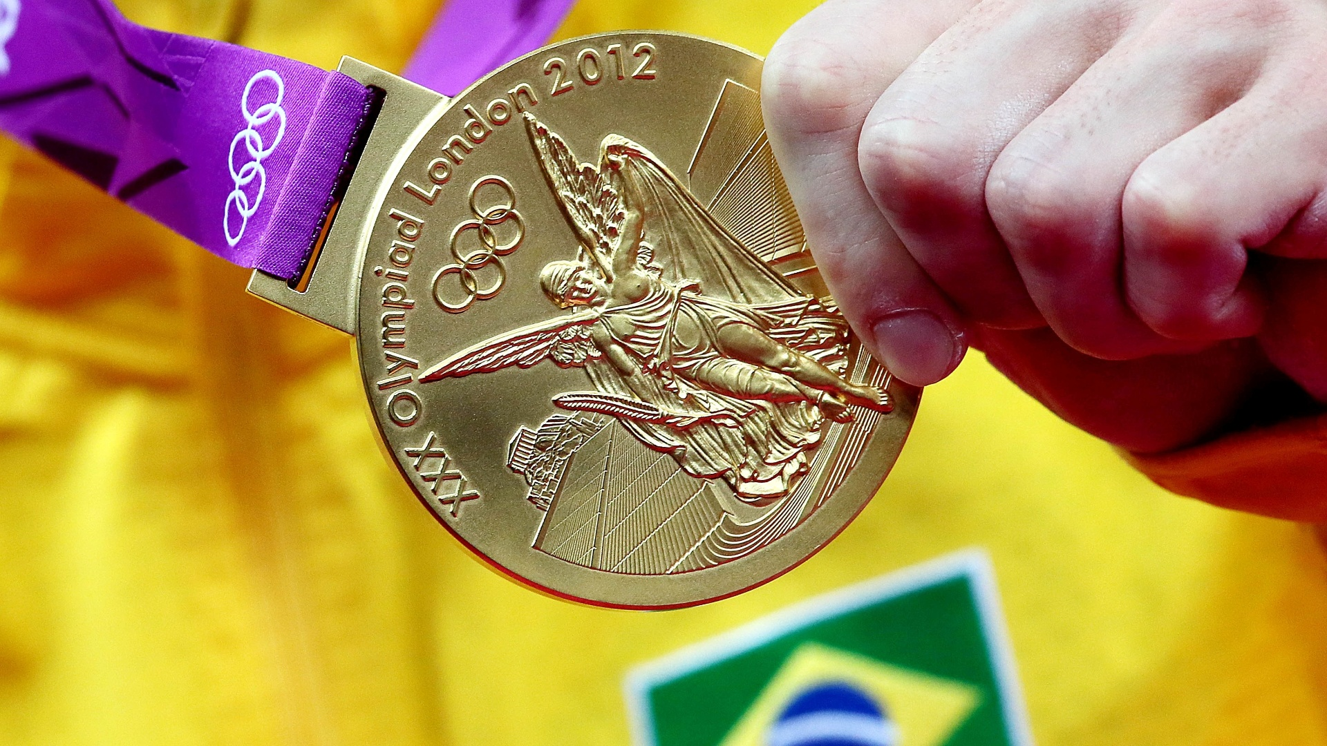 Arthur Zanetti mostra a medalha de ouro, a primeira da história da ginástica brasileira