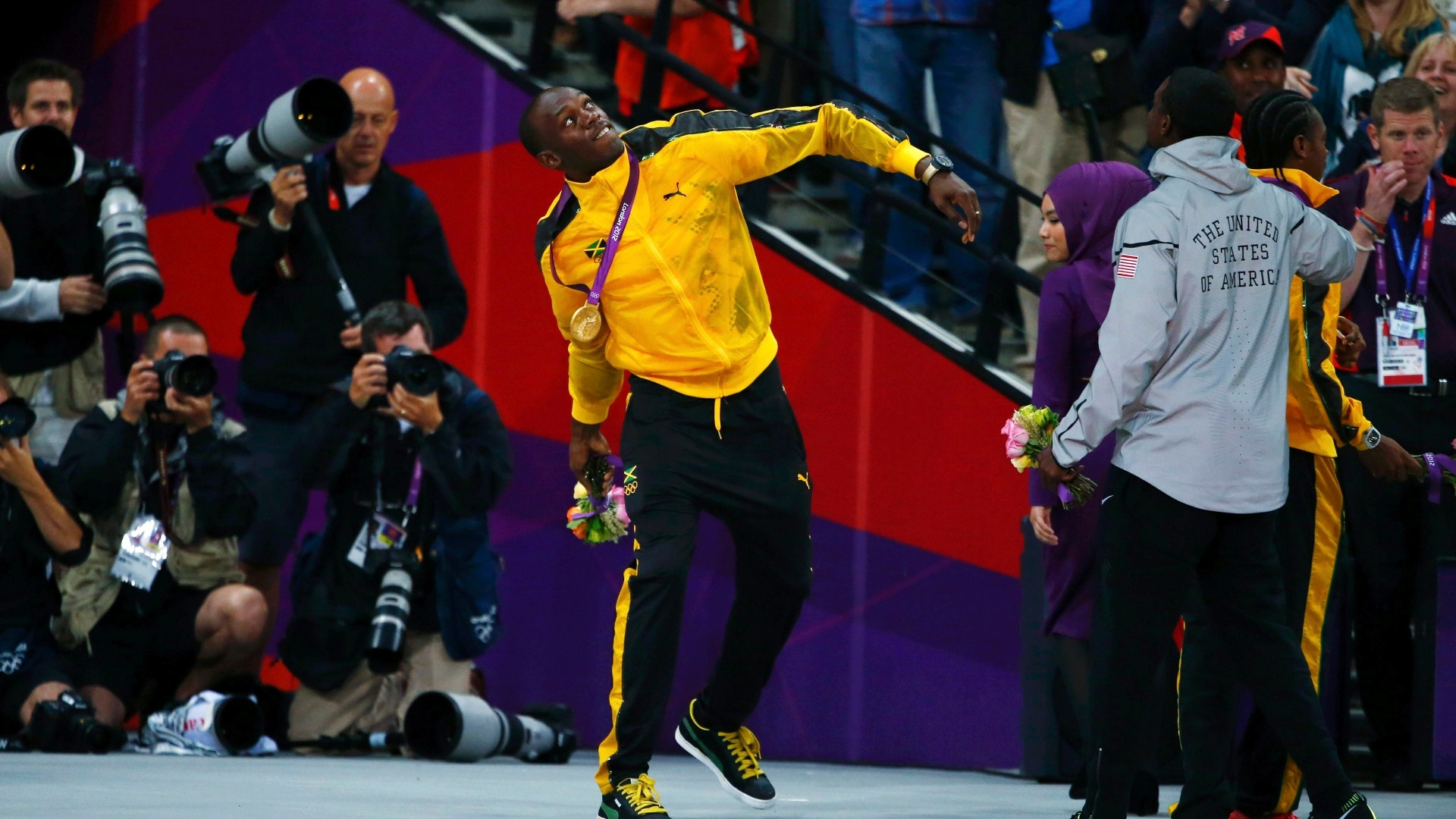 Medalhista de ouro Usain Bolt joga para o ar buqu de flores, aps cerimnia de premiao dos 100 m rasos dos Jogos de Londres