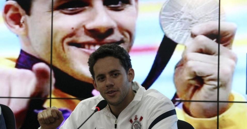 Thiago Pereira concede entrevista coletiva no CT do Corinthians, com a foto do pódio olímpico ao fundo