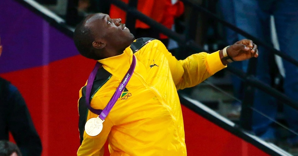 Usain Bolt arremessa para o ar buquê de flores recebido após cerimônia de premiação dos 100 m rasos