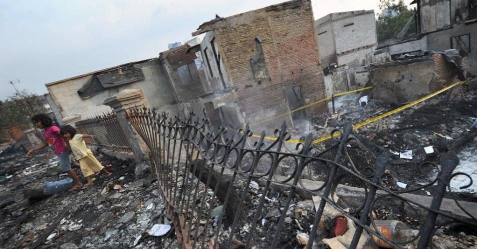 7.ago.2012 - Crianças andam em meio as casas atingidas por um incêndio em Jacarta, na Indonésia.  O fogo foi provocado por um curto na conexão elétrica. Aproximadamente 300 residências foram demolidas e mais de 1.700 pessoas deslocadas