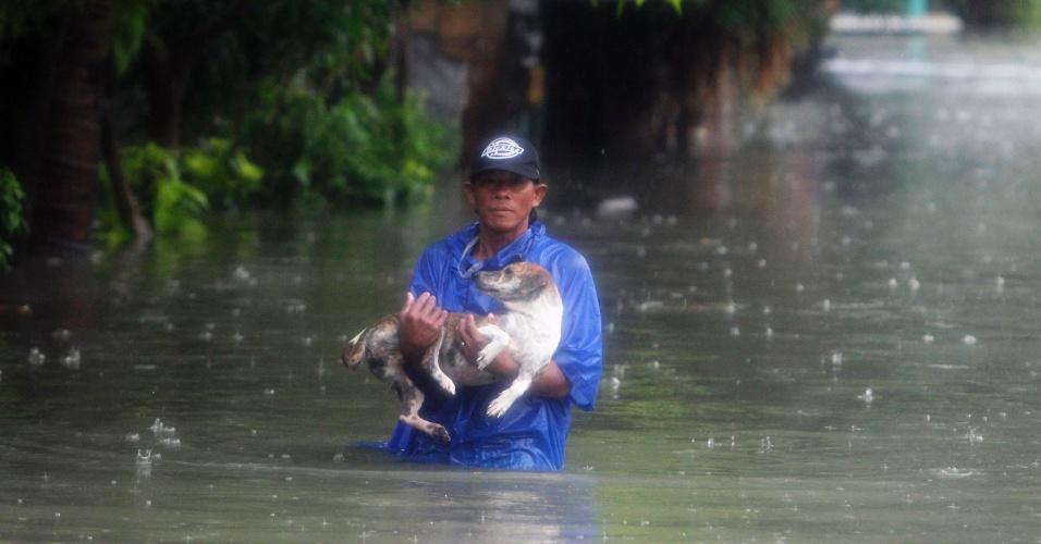 7.ago.2012 - Homem carrega cachorro em rua alagada de Las Pinas, na região metropolitana de Manila, nas Filipinas, nesta terça-feira (7). As inundações voltaram a preocupar o governo e obrigaram cidades a fecharem escolas e o comércio. Desde o início das fortes chuvas no país, 53 pessoas já morreram