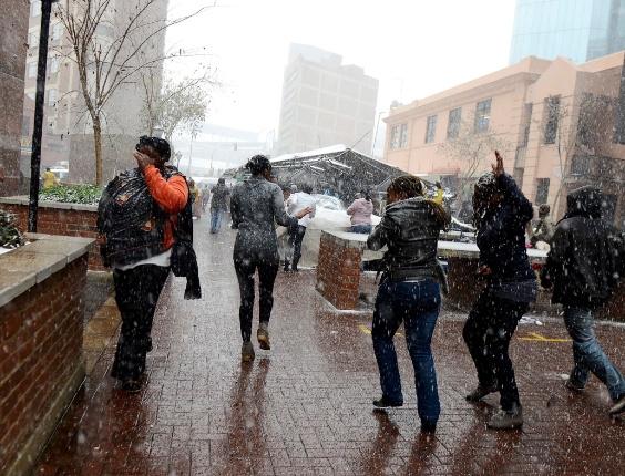 7.ago.2012 - Sul-africanos tentam se esquivar de neve que caiu em algumas partes de Joanesburgo, na África do Sul