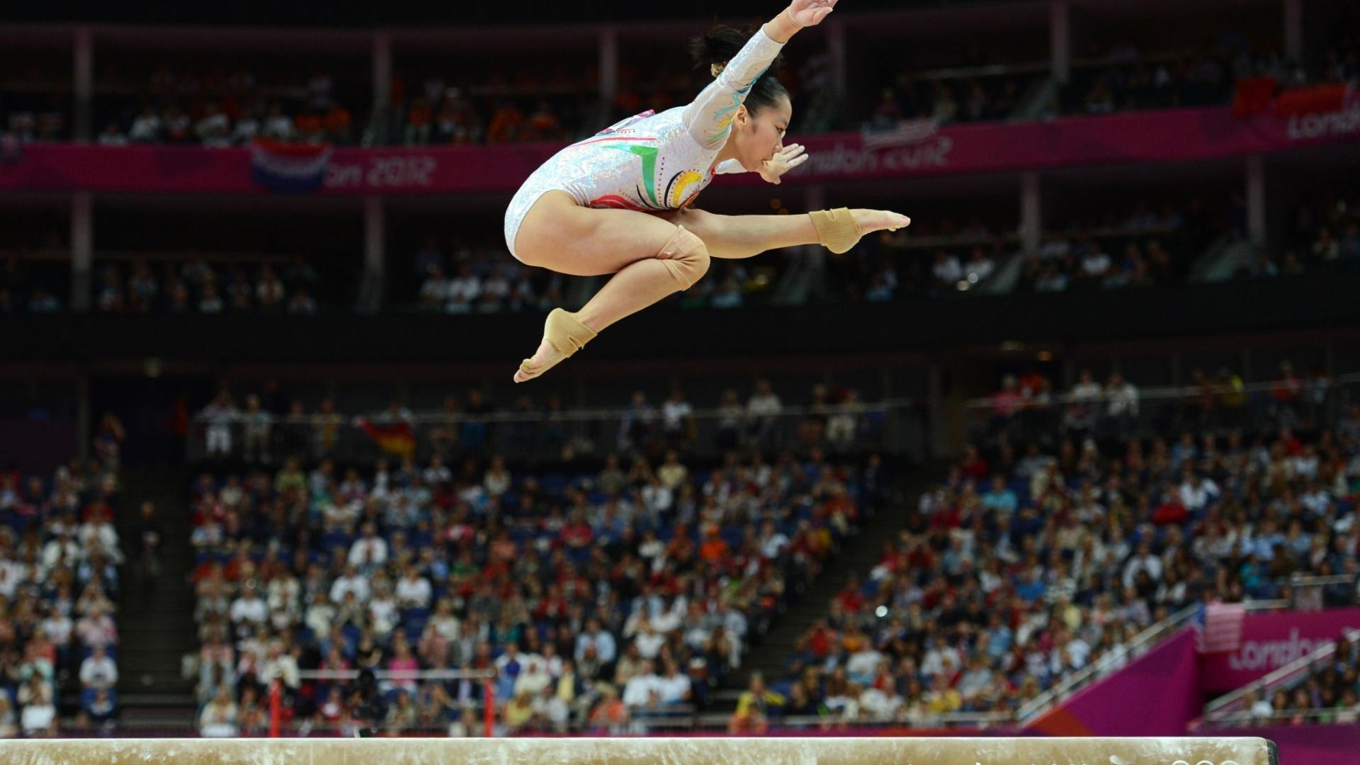 Chinesa Deng Linlin faz um alto salto coreográfico durante sua série na trave; a asiática levou a medalha de ouro na prova