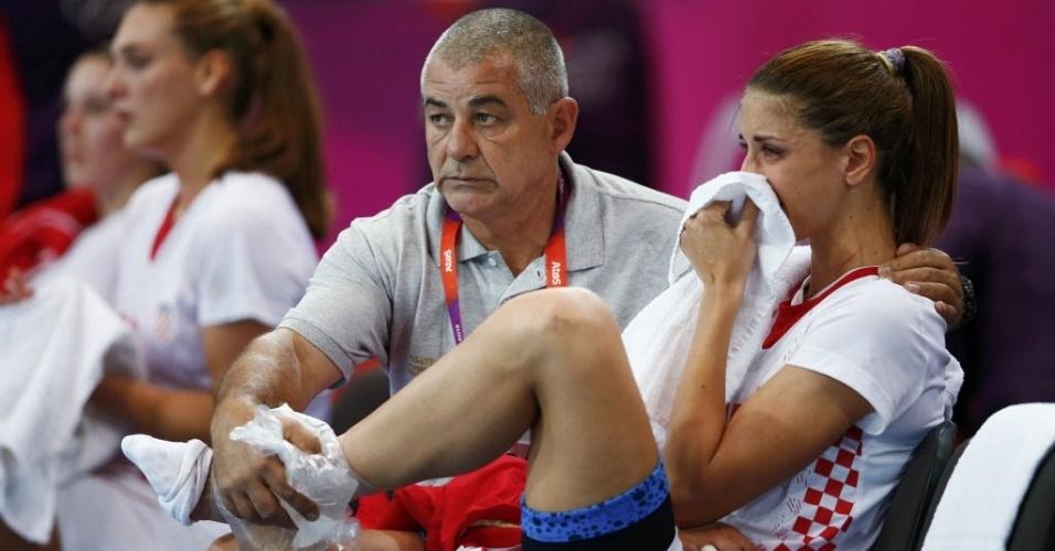 Croata Andrea Penezic chora com dores no tornozelo, enquanto vê sua seleção perder para a Espanha nas quartas de final do handebol