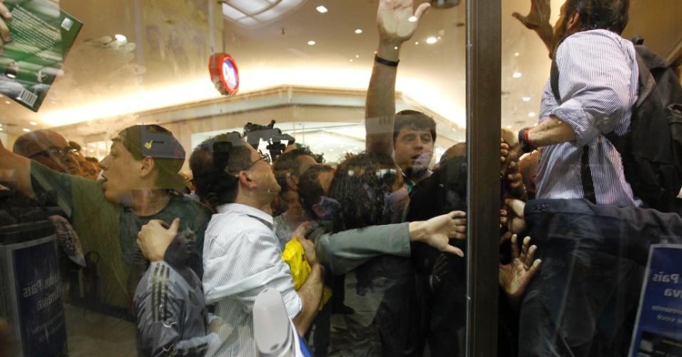 Torcedores e fãs forçam vidro da vitrine de livraria em São Paulo para tentar comprar um exemplar da biografia de Marcos