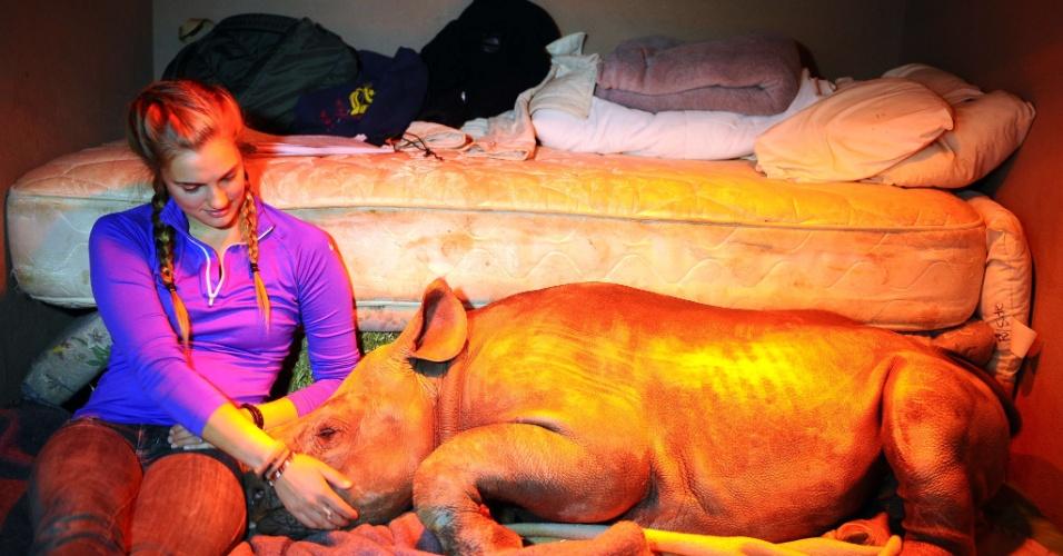 8.ago.2012 - A estudante americana Alana Russell cuida do primeiro rinoceronte a chegar ao orfanato destinado apenas a esses animais, perto de Mokopane, na África do Sul. O orfanato para rinocerontes pretende salvar os bebês cujas mães foram vítimas dos caçadores ilegais