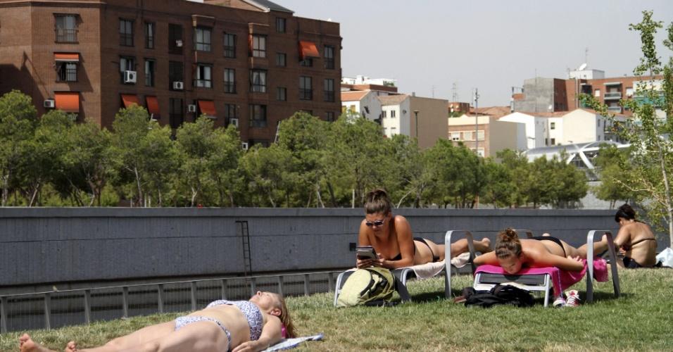 9.ago.2012 - Grupo de jovens toma sol em mais um dia de calor em Madri, na Espanha