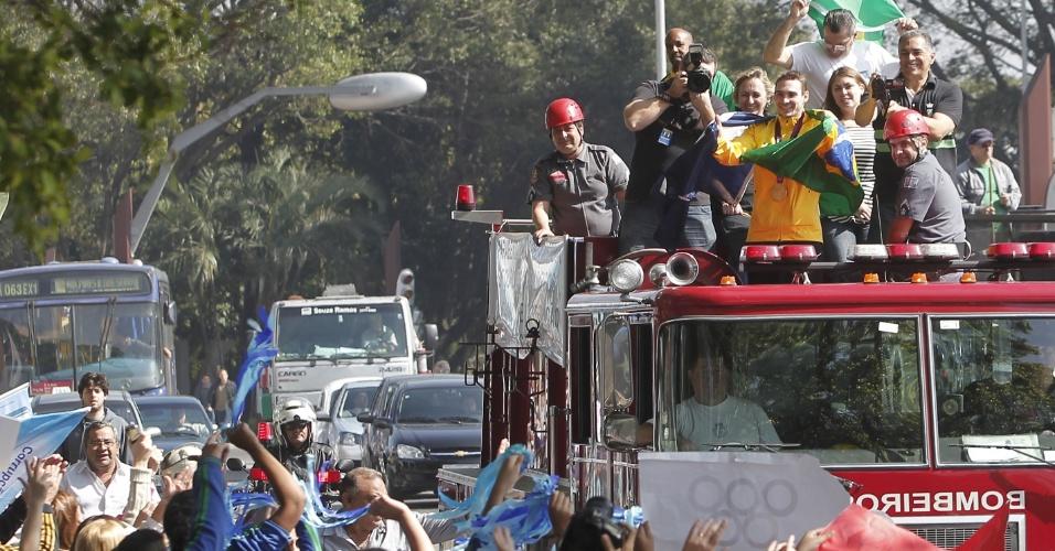 9.ago.2012 - O ginasta brasileiro Arthur Zanetti, medalhista de ouro nas argolas da ginástica artística nos Jogos Olímpicos de Londres, desfila em carro do Corpo de Bombeiros pelas ruas de São Caetano do Sul, no ABC Paulista, nesta quinta-feira (9)