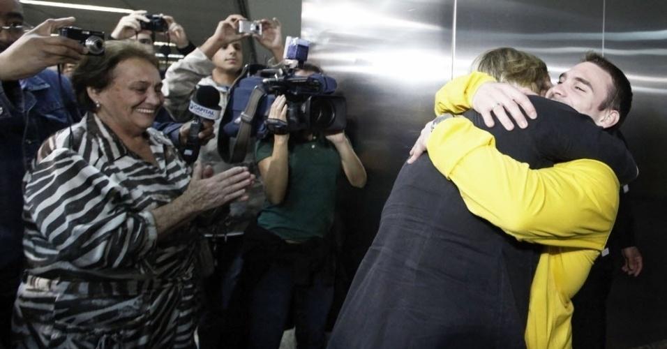 Arthur Zanetti abraça a mãe Roseane na chegada ao aeroporto, enquanto a avó (à esq.) aplaude o neto medalhista de ouro