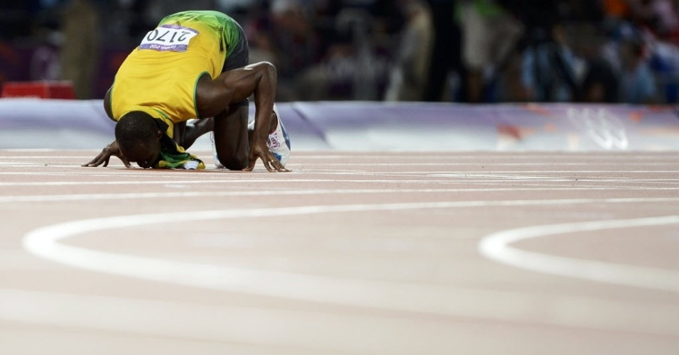 Usain Bolt beija o chão do Estádio Olímpico de Londres ao conquistar o bicampeonato olímpico dos 200 m