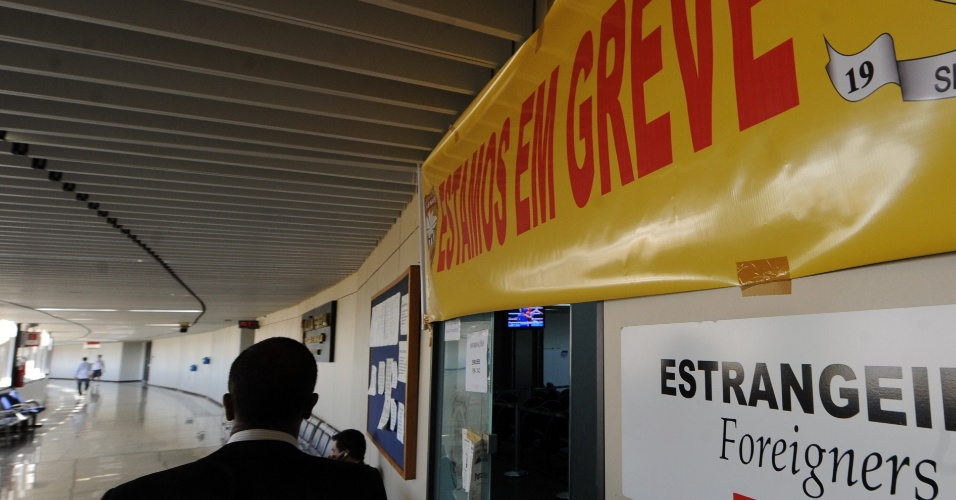 10.ago.2012 - Cartaz onde se l&#234; &#34;estamos em greve&#34; &#233; pendurado em frente ao departamento da Pol&#237;cia Federal no aeroporto internacional Tom Jobim, no  Rio de Janeiro. A greve da categoria come&#231;ou no dia 7