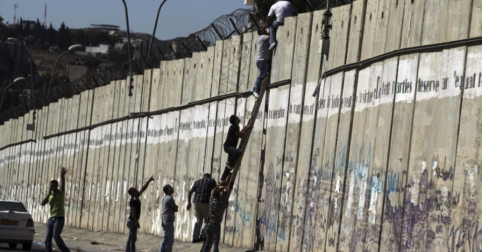 10.ago.2012 -  Com ajuda de uma escada, palestinos tentam pular muro que divide a Cisjord&#226;nia de Israel, no norte de Jerusal&#233;m, para poder assistir &#224;s ora&#231;&#245;es do Ramad&#227;, na mesquita de Al Aqsa. Devido &#224; idade, esses palestinos foram proibidos por Israel de cruzar Jerusal&#233;m, o que &#233; permitido apenas para maiores de 40 anos e menores de 12