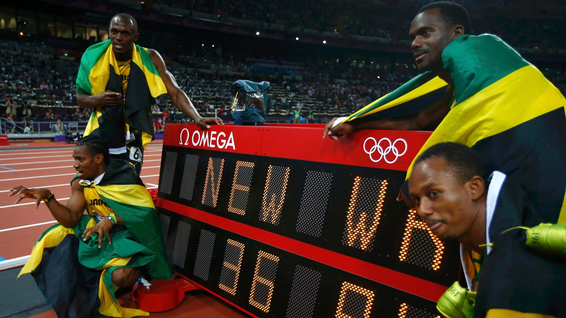 Equipe jamaicana do revezamento 4x100 m comemora medalha de ouro e novo recorde mundial ao lado de marca