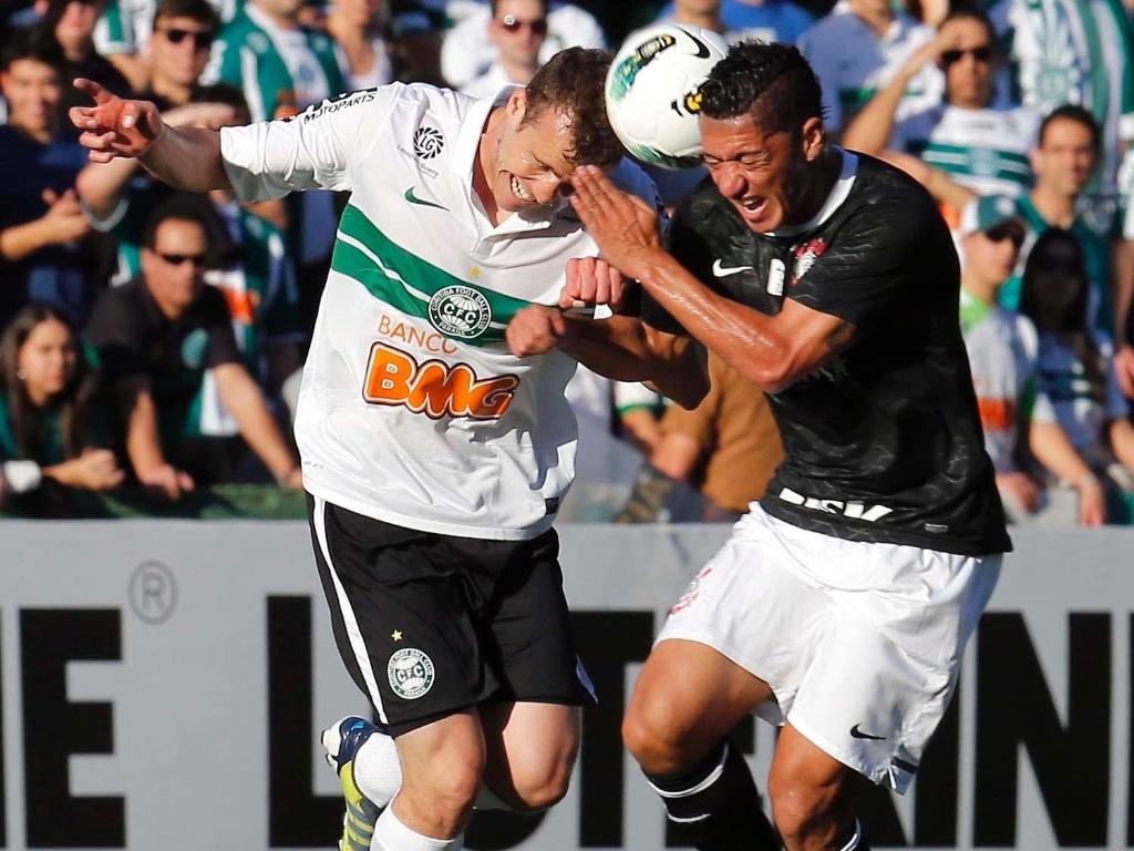 Chico, do Coritiba, e Ralf, do Corinthians, em lance durante a partida, válida pela Série A do Campeonato Brasileiro no Couto Pereira