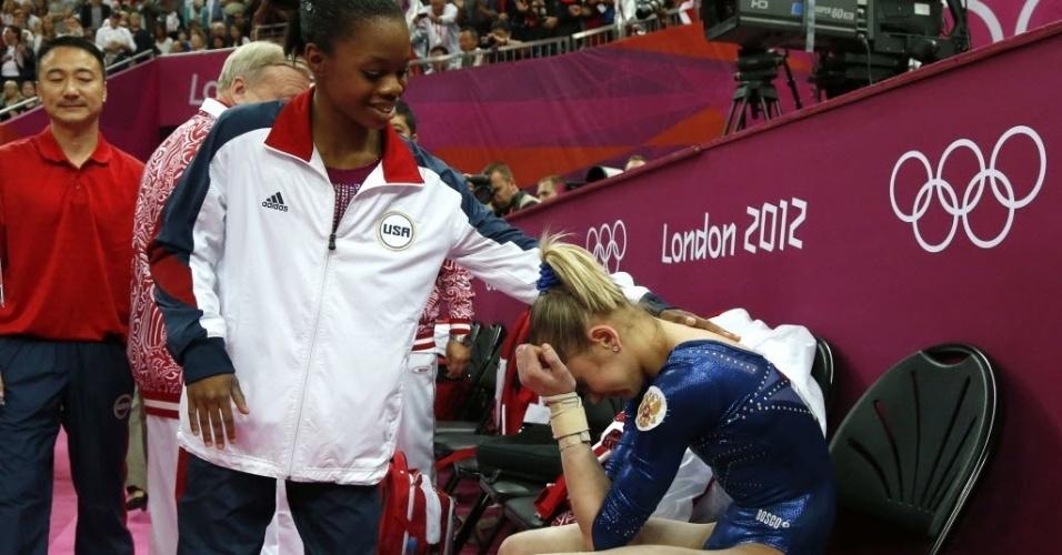 Gabrielle Douglas, dos EUA, vence prova na ginástica e tenta confortar a russa Victoria Komova, que ficou em segundo