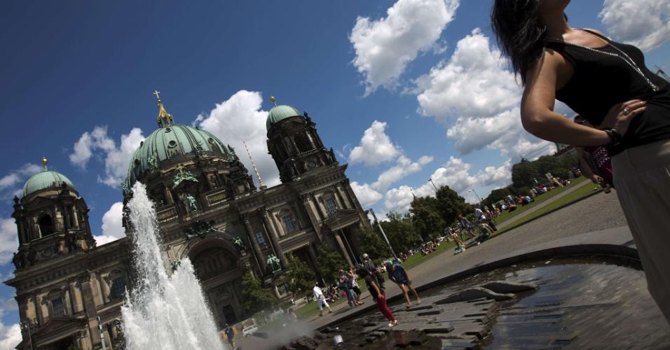 13.ago.2012 - Mulher posa para foto diante de fonte de catedral em Berlim, capital da Alemanha, nesta segunda-feira (13)