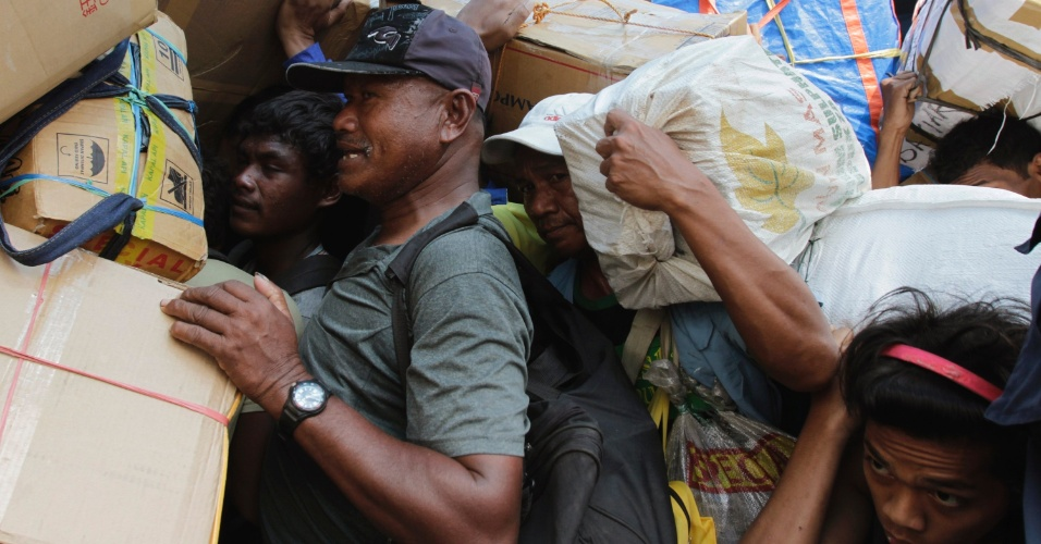 13.ago.2012 - Passageiros carregam bagagens e tenam entrar a bordo do navio que vai levá-los de volta para casa, em Tanjung Priok, em Jacarta. Centenas de muçulmanos devem deixar a capital da Indonésia para celebrar o feriado Eid al-Fitr, que marca o fim do Ramadã, o mês sagrado dos muçulmanos, nos dias 19 e 20 de agosto