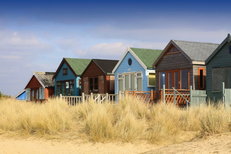 Cabanas de praia na Inglaterra, em cores diversas e basicamente feitas de madeira