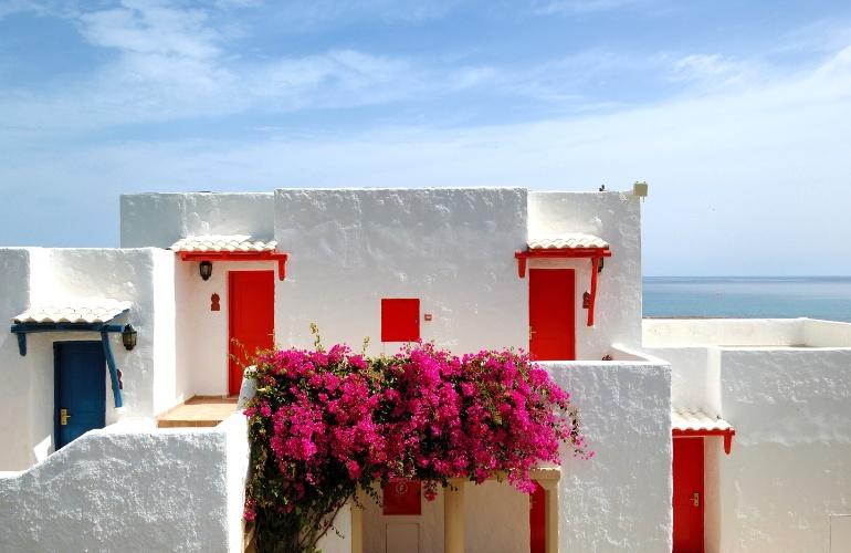 Casas gregas tradicionais, com paredes caiadas, telhado ausente e esquadrias em cores vivas