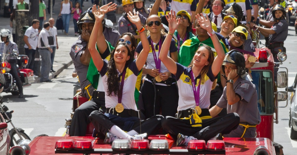Jogadoras da seleção brasileira feminina de vôlei acenam para o público durante carreata em São Paulo