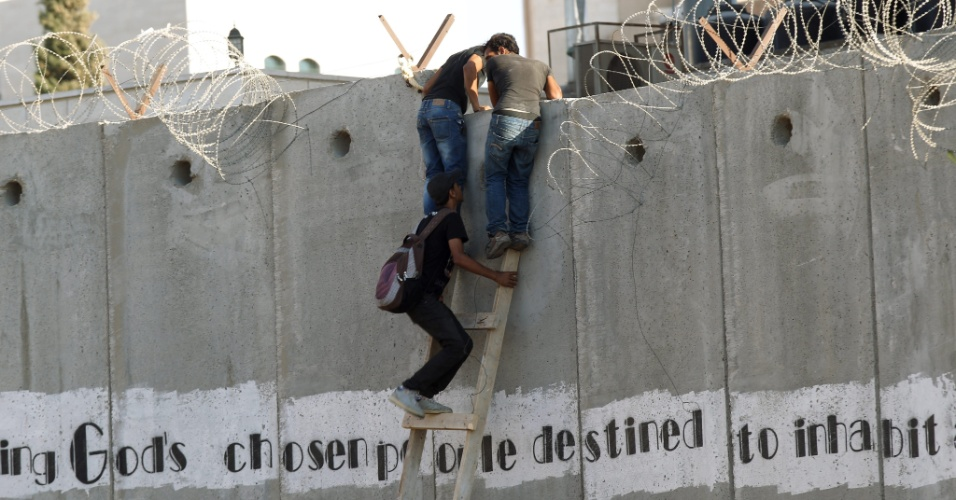 14.ago.2012 - Homens usam escada para cruzar o muro de separação em A-Ram, na Cisjordânia, perto do posto de controle de Kalandia, para poder assistir às orações da noite na mesquita de Al-Aqsa, no 27º dia do mês de Ramadã