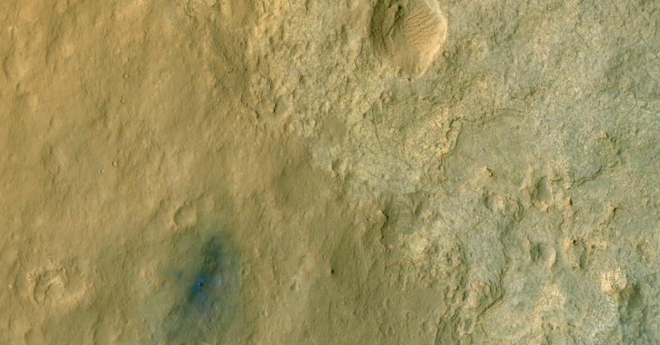 14.ago.2012 - O jipe-robô Curiosity pousa dentro da cratera de Marte em foto feita pela HiRISE, câmera de alta resolução da Nasa (agência espacial americana). A mancha azulada no canto da imagem mostra a chegada do equipamento de exploração ao planeta ? as cores usadas dão mais profundidade e melhor resolução, o que ajuda a diferenciar as sutis variações que existem pelo terreno. A parte de baixo da imagem, que traz o monte Sharp, só deverá ser divulgada nos próximos cinco dias.
