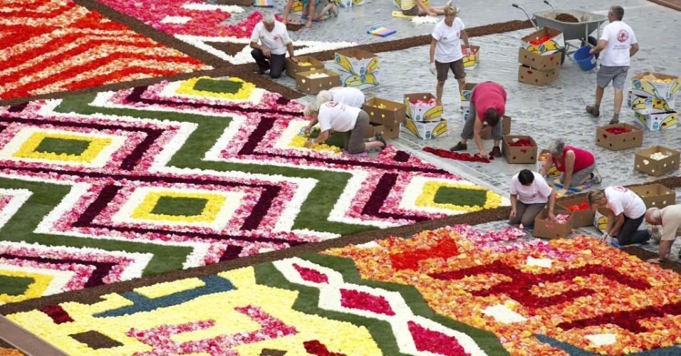 14.ago.2012 -  Voluntários preenchem com begônias os espaços restantes para compor o tradicional tapete floral, que a cada dois anos, desde 1971, é montado na Grande Praça de Bruxelas, na Bélgica