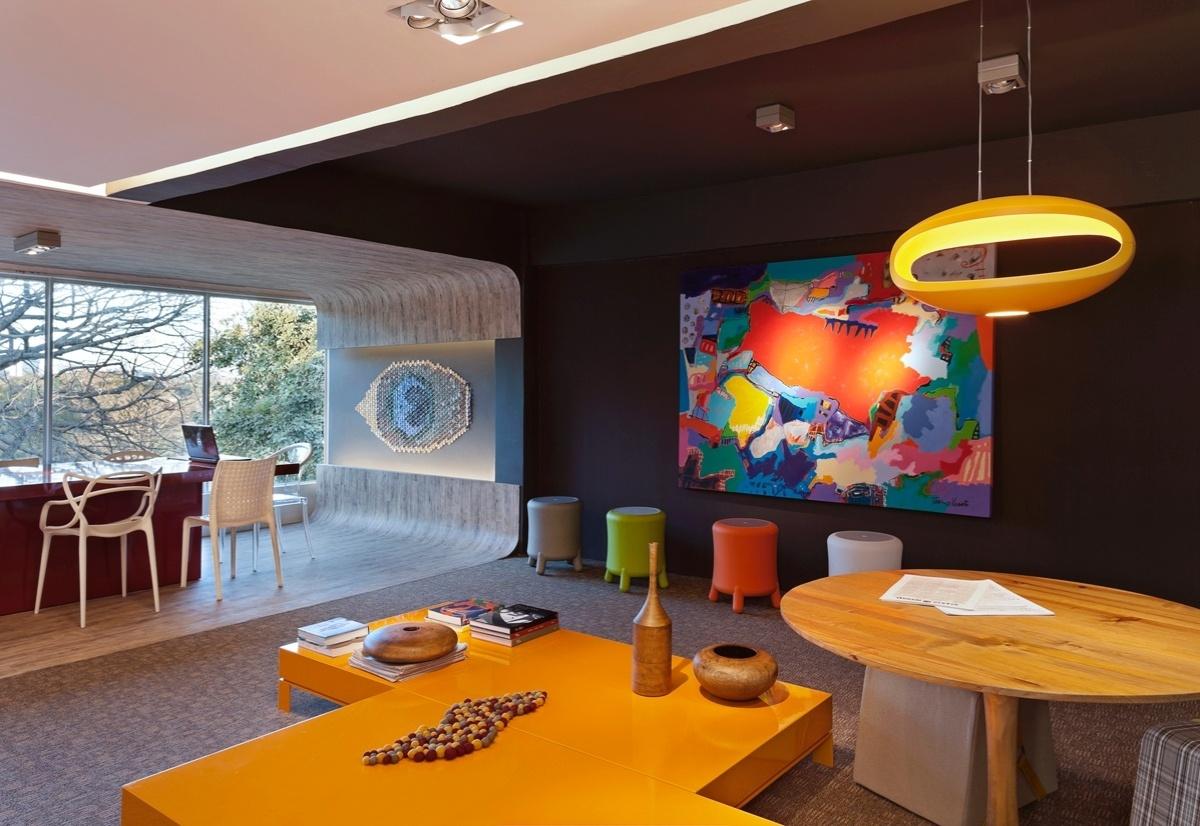 Sala de Imprensa assinada por Heloíza Alcoforado e Rafaella Alcoforado para a 6ª edição da Morar Mais, em Brasília (14/08 a 23/09/2012): a mesa de centro amarela é combinada a outros elementos de cores fortes (como a luminária e os banquinhos) e às obras de arte