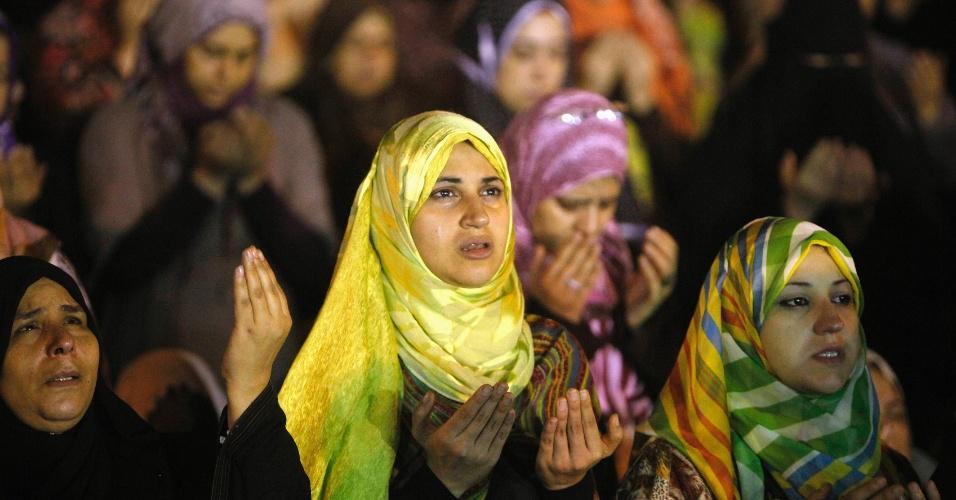 15.ago.2012 Mulheres muçulmanas realizam orações noturnas durante o mês sagrado do Ramadã, fora de uma mesquita no Cairo