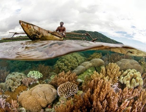 Homem passa de barco sobre os corais e os recifes da costa de Raja Ampat, na Indonésia
