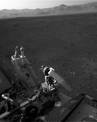 17.ago.2012 - A imagem, divulgada pela Nasa (agência espacial americana), mostra parte do robô Curiosity. A borda da cratera Gale está localizada na parte mais clara da fotografia