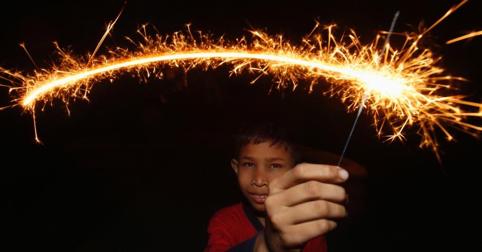 18.ago.2012 - Criança muçulmana brinca com fogo em Bahau, na Malásia, em comemoraçãoao fim do mês sagrado do Ramadã