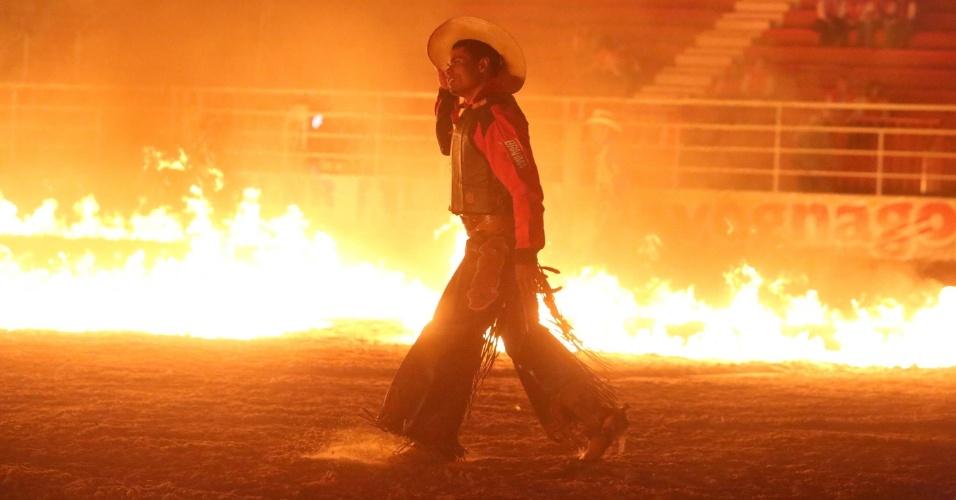 18.ago.2012 - Peão atravessa arena em chamas na Festa do Peão de Barretos (SP), que teve início na noite de quinta-feira (16)