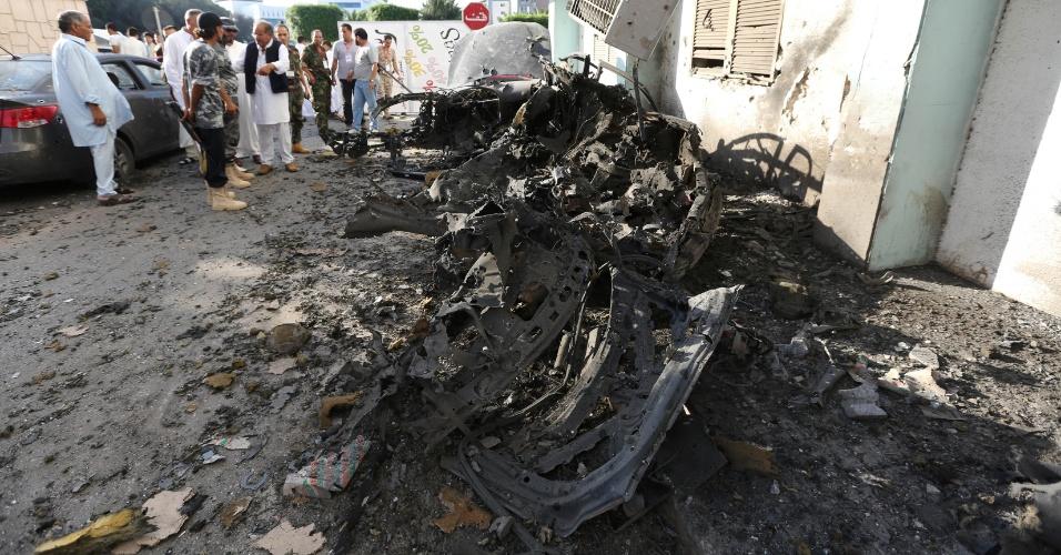 19.ago.2012 - Forças de segurança da Líbia inspecionam destroços de veículo perto do Ministério do Interior de Trípoli