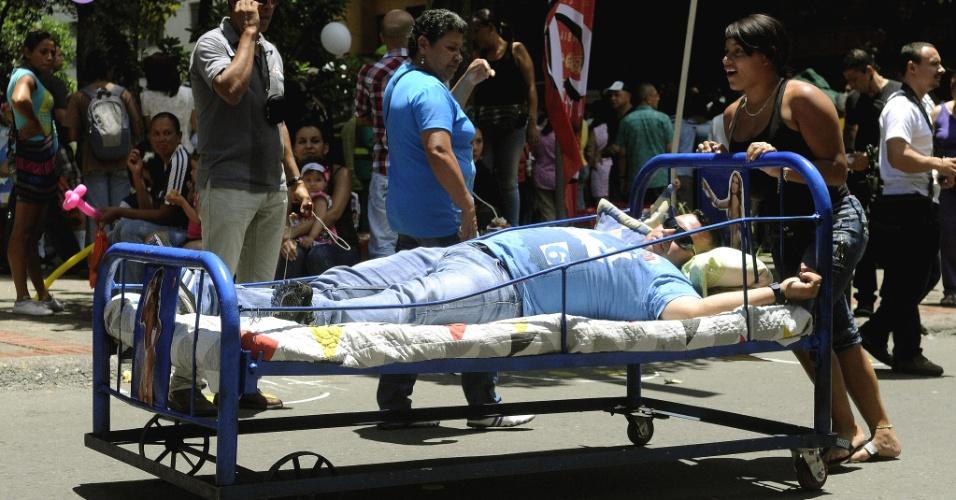 19.ago.2012 - Homem deita em cama que é empurrada por uma mulher durante a comemoração do ''Dia Mundial da Preguiça'' em Itagüí, na Colômbia