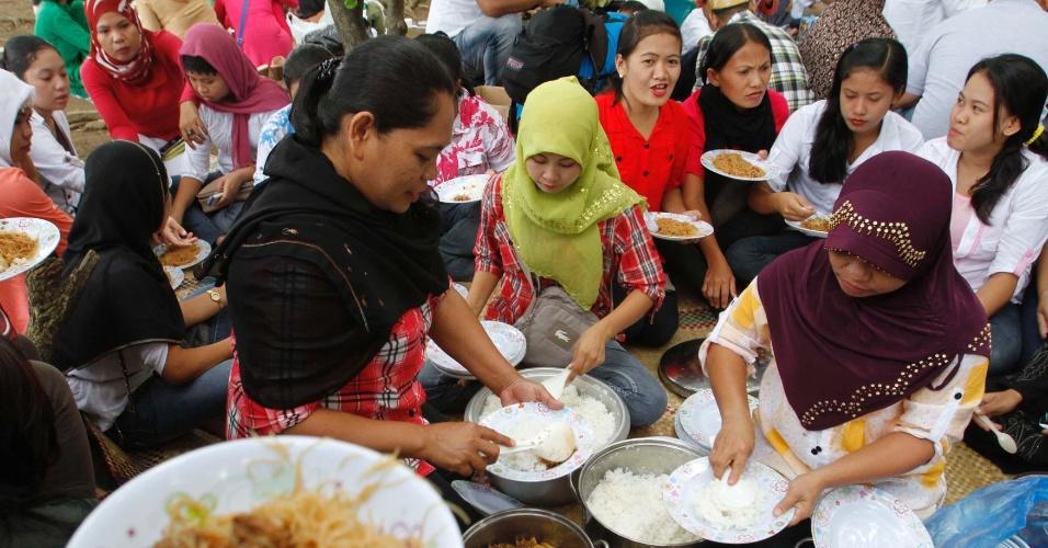 19.ago.2012 - Muçulmanas partilham refeição neste domingo (19) após sessão de orações para celebrar o Eid al-Fitr, festividade que comemora o fim do mês sagrado Ramadã, em Manila, nas Filipinas