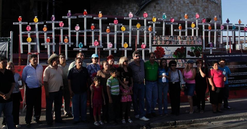 19.ago.2012 - Parentes e amigos posam para foto na frente de cassino após afixar cruzes com nomes de vítimas de um ataque no local, que fica em Monterrey, no Estado mexicano de Nuevo León, no dia 25 de agosto de 2011