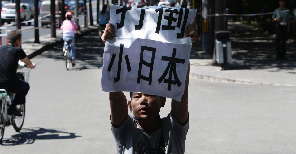"""19.ago.2012 - Segurando cartaz onde se lê a mensagem """"Destitua o Japão pequeno"""", homem faz protesto anti-Japão em frente ao prédio da embaixada japonesa em Pequim, na China"""