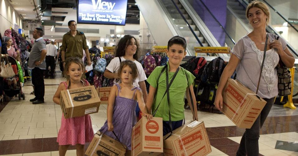 19.ago.2012 - Uma família carrega kits de máscaras de gás em um shopping de Jerusalém, Israel