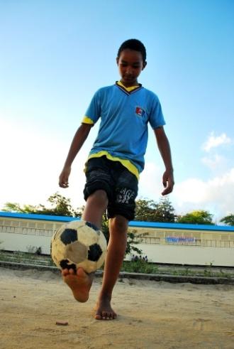 O estudante Kayã Rodrigues, da escola Estadual Dom Pedro II, localizada no Cepa (Centro Educacional de Pesquisas Aplicada), no Farol, em Maceió, brinca de uniforme e de pés no chão com a bola em horário de aula