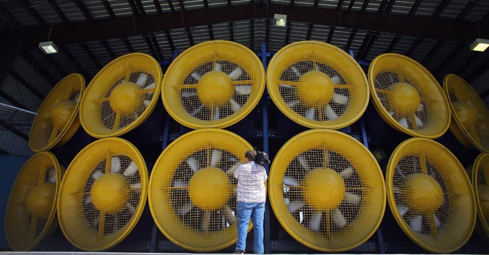 21.ago.2012 - Um cinegrafista encara a parede de vento do centro de engenharia da Universidade Internacional da Flórida, nos Estados Unidos. Os 12 ventiladores têm 8.400 cavalos de potência e são capazes de simular um furacão com ventos de até 252 km/h ? o experimento serve para testar a resistência de casas e materiais