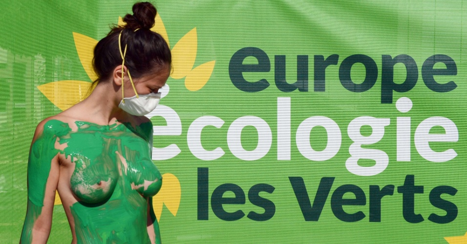 """22.ago.2012 - Mulher pinta seu corpo nu de verde em evento do partido verde francês em Poitiers, no centro-oeste do país. Grupo protesta contra o """"Greenwashing"""", termo que designa o marketing empresarial ou político que manipula dados em prol de uma falsa imagem sustentável e responsável"""