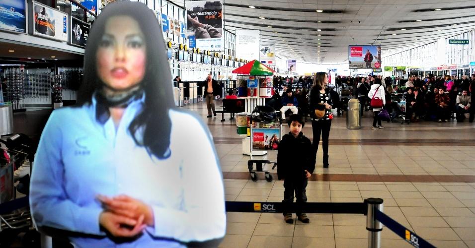 22.ago.2012 - Passageiros observam holograma no Aeroporto Internacional de Santiago, no Chile. O aeroporto recentemente instalou hologramas, de tamanho real, que projetam a imagem de um funcionário do local para fornecer informações aos visitantes. Ela, basicamente, informa os passageiros sobre os itens proibidos de embarcar
